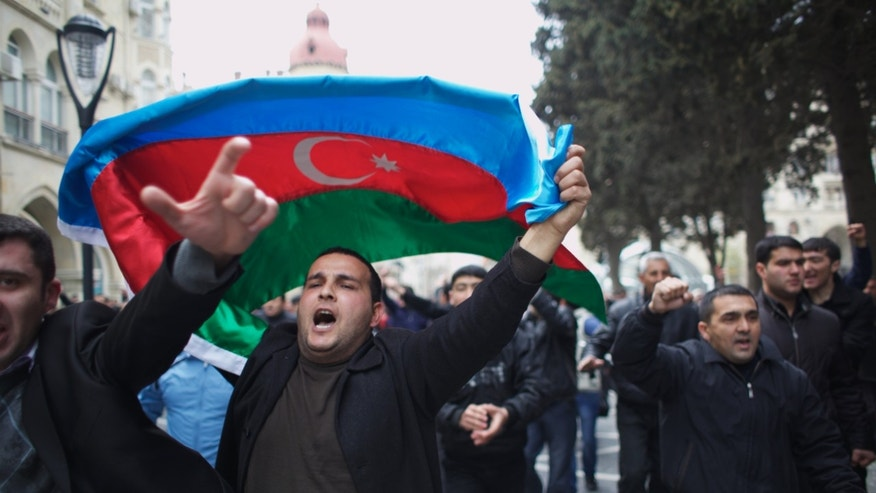 FILE - In this Saturday, April 2, 2011 file photo protesters wave national flags as they rally in Baku, Azerbaijan. International rights groups have accused Azerbaijani President Ilham Aliyev's government of pressuring and harassing government critics. (AP Photo/Ilkin Huseynov, File)