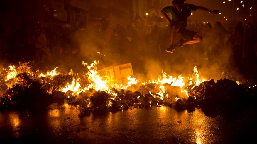 A demonstrator with his face covered jumps over a burning barricade at the Cinelandia square during a march in support of teachers on strike in Rio de Janeiro, Brazil, Monday, Oct. 7, 2013. Teachers have been on strike demanding better pay for almost two months. (AP Photo/Felipe Dana)