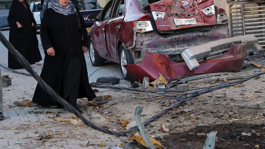 Women walk past the aftermath of a car bomb attack in the mainly Shiite neighborhood of Zafaraniyah in southeastern Baghdad, Iraq, Tuesday, Oct. 8, 2013. Deadly attacks in Iraq killed tens of people on Monday. The attacks are the latest in a relentless wave of killing that has made for Iraq's deadliest outburst of violence since 2008. (AP Photo/ Hadi Mizban)