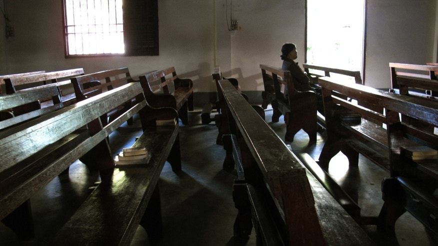 In this Tuesday, Sept. 24, 2013 photo, a worshipper sits in a church ahead of an afternoon mass in the Vietnamese central highland town of Pleiki. Communist Vietnam allows state-sanctioned faiths to grow, but continues to keep a close watch on all religious institutions. (AP Photo/Chris Brummitt)