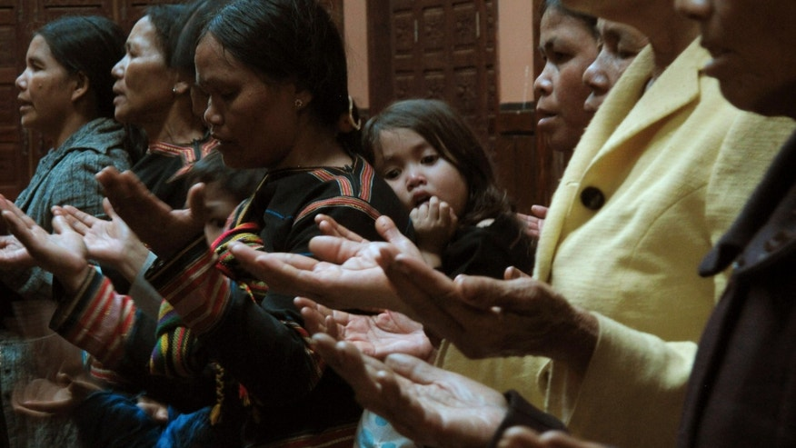 In this Wednesday, Sept. 25, 2013 photo, members of a Vietnamese ethnic minority group worship at a church in the Vietnamese central highland town of Pleiku. Communist Vietnam allows state-sanctioned faiths to grow, but continues to keep a close watch on all religious institutions. (AP Photo/Chris Brummitt)