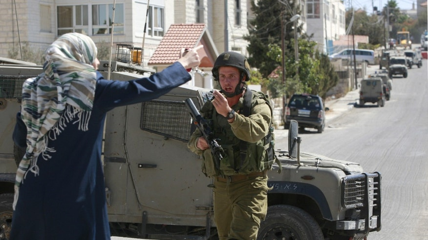 A Palestinian woman argues with an Israeli soldier blocking the road during an army operation in the West Bank city of Ramallah, Monday, Oct. 7, 2013. An Israeli army force surrounded a house and arrested two Palestinian men while clashing with angry residents throwing stones before withdrawing out of the city. (AP Photo/Majdi Mohammed)