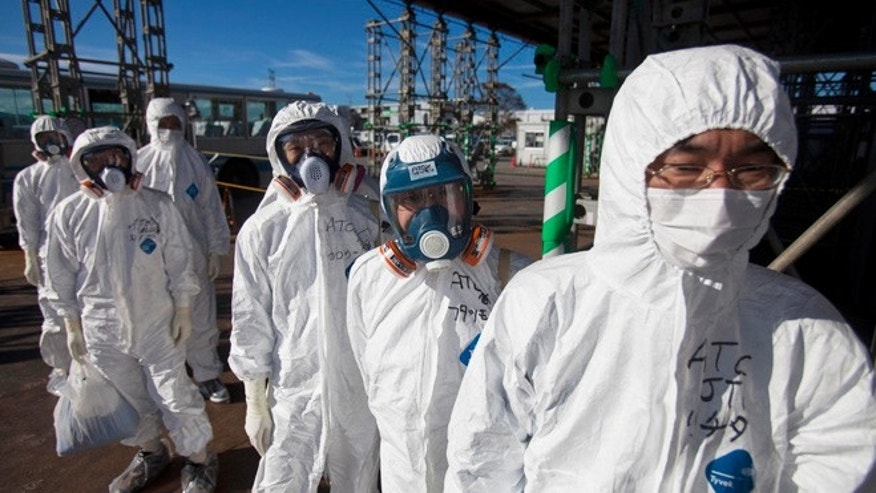 Nov. 12, 2011: In this file photo, workers in protective suits and masks wait to enter the emergency operation center at the crippled Fukushima Dai-ichi nuclear power station in Okuma, Japan as the media were allowed into Japan's tsunami-damaged nuclear power plant for the first time since the March 11 disaster.
