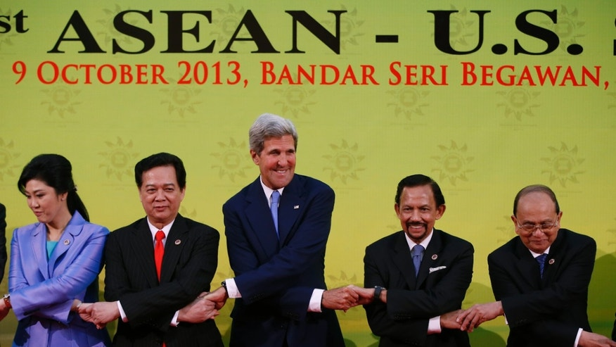 U.S. Secretary of State John Kerry, center, chains his hands with the Association of Southeast Asian Nations leaders, Thai Prime Minister Yingluck Shinawatra, left, Vietnamese Prime Minister Nguyen Tan Dung, second  left, Brunei Sultan Hassanal Bolkiah, second right, and Myanmar President Thein Sein, for a group photo before the 1st ASEAN - U.S. Summit in Bandar Seri Begawan, Brunei, Wednesday, Oct. 9, 2013. (AP Photo/Vincent Thian)
