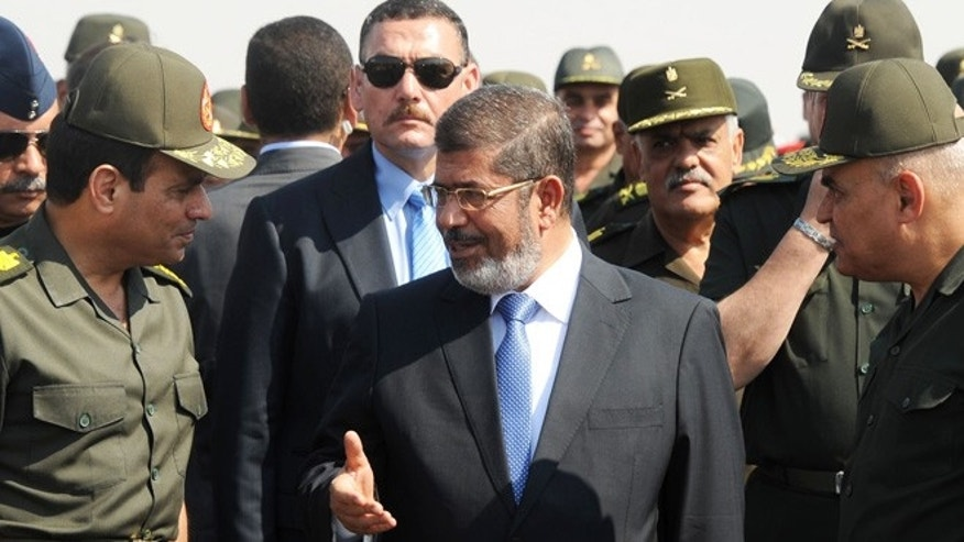 Oct. 10, 2012: In this file photo released by the Egyptian Presidency, then Egyptian President Mohammed Morsi, center, speaks with Minister of Defense, Lt. Gen. Abdel-Fattah el-Sissi, left, at a military base in Ismailia, Egypt. An Egyptian court has set Nov. 4, 2013, as the start date for the trial of ousted President Mohammed Morsi on charges of incitement to murder for the killings of opponents who were rallying outside his palace while he was in office.