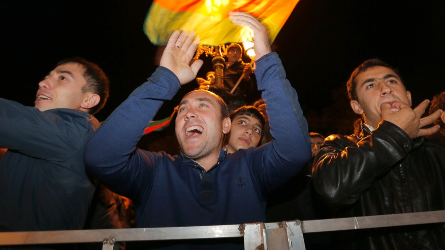 Supporters of Azerbaijan's President Ilham Aliyev celebrate his victory in the presidential elections in Baku, Azerbaijan, Wednesday, Oct. 9, 2013. Azerbaijan's president won a third five-year term by a landslide in Wednesday's vote, according to an exit poll, extending decades of dynastic rule in the oil-rich Caspian Sea nation allied with the West. (AP Photo/Sergei Grits)