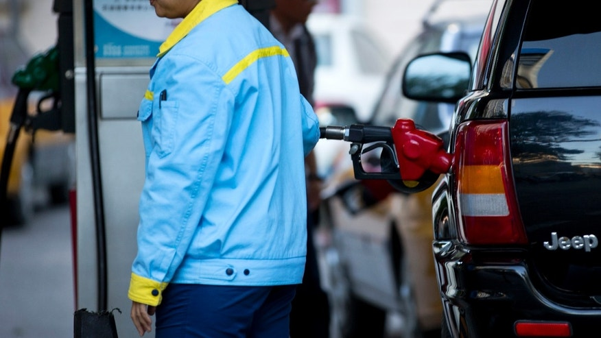 A petrol attendant fills a car at a China National Petroleum Corporation (CNPC) petrol station in Beijing, China Thursday, Oct. 10, 2013. China passed the United States in September as the world's biggest net oil importer, driven by faster economic growth and strong auto sales, according to U.S. government data released this week. (AP Photo/Andy Wong)