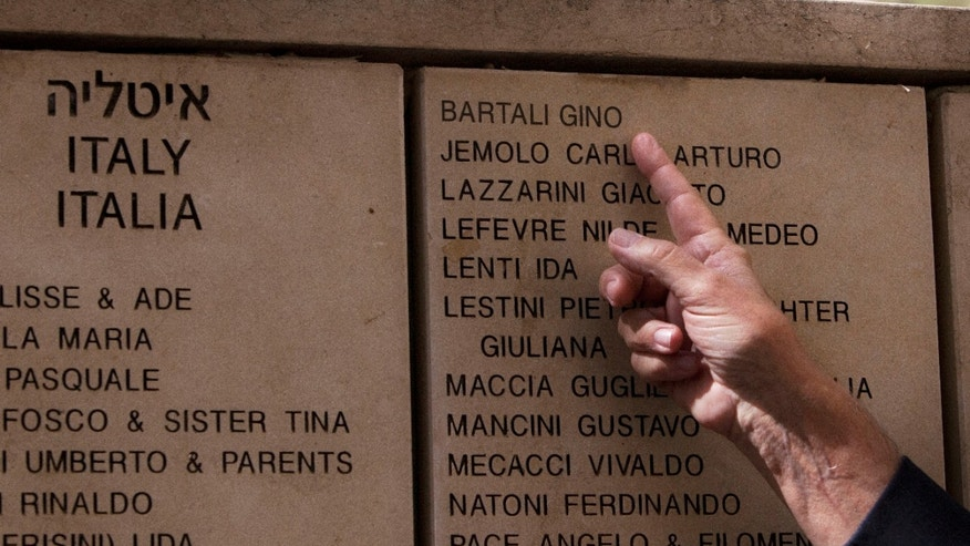 Italian Andrea Bartali son of champion cyclist Gino Bartali, points at the name of his father at the Hall of Names at the Yad Vashem Holocaust memorial in Jerusalem,  Thursday, Oct. 10, 2013, after a ceremony to induct Bartali into the prestigious Garden of the Righteous Among the Nations for his help rescuing Jews during World War II. During the German occupation of Italy, the champion cyclist aided the Jewish-Christian rescue network in his hometown of Florence and the surrounding area by shuffling forged documents and papers hidden in the tubes and seat of his bike. (AP Photo/Sebastian Scheiner)