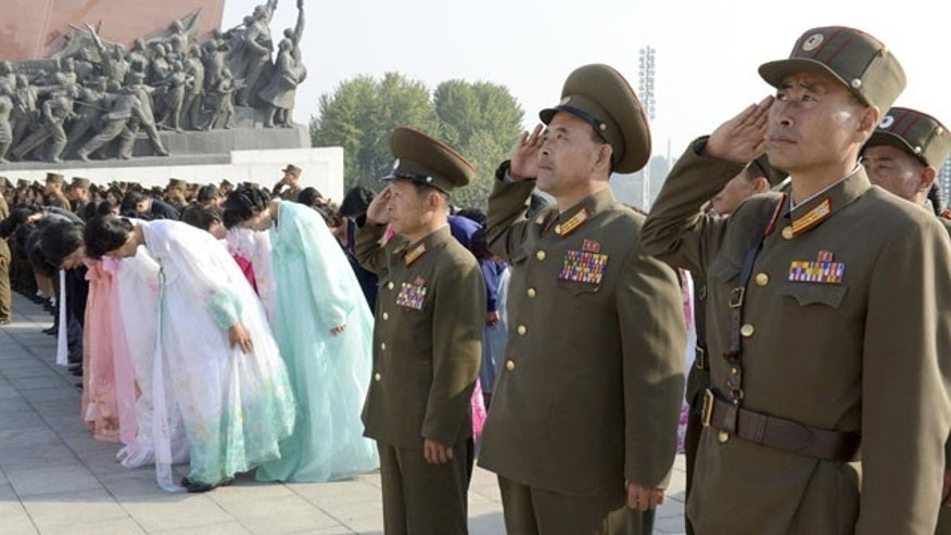 October 10, 2013: North Korean soldiers salute the statues of late leaders, Kim Il Sung, and Kim Jong Il on Mansudae to mark the 68th anniversary of the founding of the ruling Workers' Party of Korea, in Pyongyang, North Korea Thursday. (AP Photo/Kyodo News)