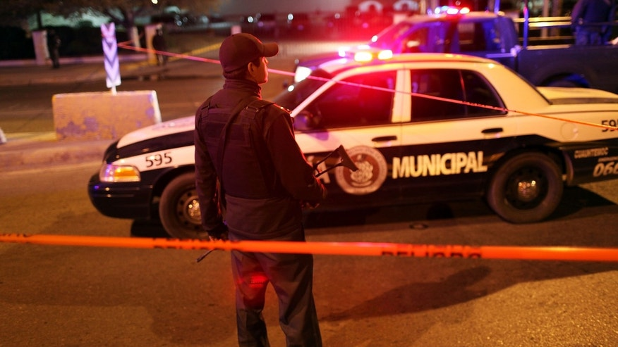 JUAREZ, MEXICO - MARCH 26:  Police gather at an early morning murder, one of numerous murders over a 24 hour period, on March 26, 2010 in Juarez, Mexico. Secretary of State Hillary Rodham Clinton, Defense Secretary Robert Gates, and Homeland Security Secretary Janet Napolitano all visited Mexico on March 23 for discussions centered on Mexico's endemic drug-related violence. The border city of Juarez, Mexico has been racked by violent drug related crime recently and has quickly become one of the most dangerous cities in the world to live. As drug cartels have been fighting over ever lucrative drug corridors along the United States border, the murder rate in Juarez has risen to 173 slayings for every 100,000 residents. President Felipe Calderon's strategy of sending 7000 troops to Juarez has not mitigated the situation. With a population of 1.3 million, 2,600 people died in drug-related violence last year and 500 so far this year, including two Americans recently who worked for the U.S. Consulate and were killed as they returned from a children's party.  (Photo by Spencer Platt/Getty Images)