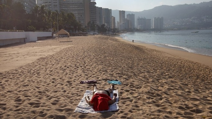 ACAPULCO, MEXICO - MARCH 02:  A lone tourist lies out on the beach early on March 2, 2012 in Acapulco, Mexico. Drug violence surged in the coastal resort last year, making Acapulco the second most deadly city in Mexico after Juarez. One of Mexico's top tourist destinations, Acapulco has suffered a drop in business, especially from foreign tourists, due to reports of the violence. Toursim accounts for some 9 percent of Mexico's economy and about 70 percent of the output of Acapulco's state of Guerrero.  (Photo by John Moore/Getty Images)