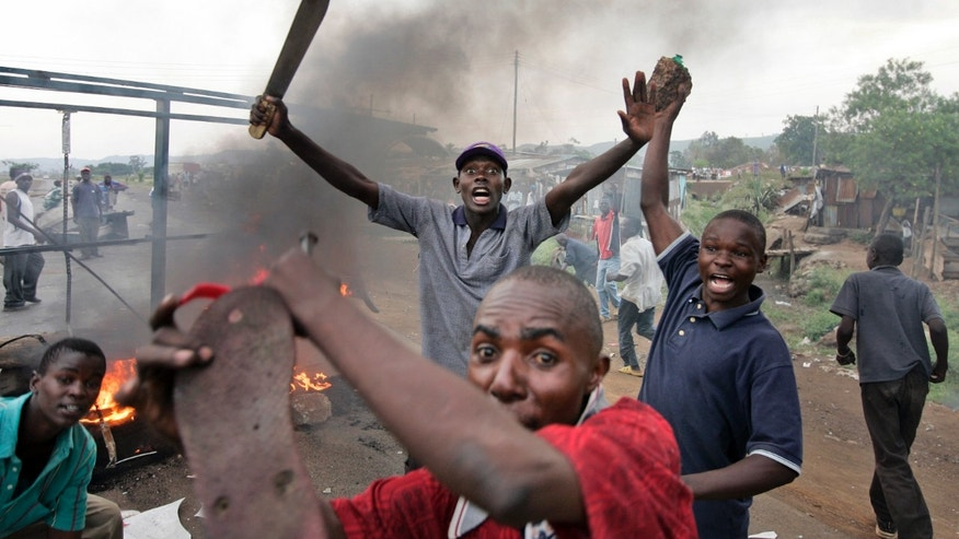 FILE - In this Monday, Jan. 28, 2008 file photo, Kenyan men from the Luo tribe armed with machetes and rocks enforce a makeshift roadblock, searching passing vehicles for Kikuyus trying to flee the town in order to kill them, during post-election violence on the main road to the Ugandan border near the airport in Kisumu, Kenya. Kenya's foreign minister Amina Mohamed said at a news conference Wednesday, Oct. 9, 2013 that no sitting president in the world has had to appear before a court, a statement that comes as Kenya appears to be laying the groundwork to avoid having President Uhuru Kenyatta appear at the International Criminal Court next month. (AP Photo/Ben Curtis, File)