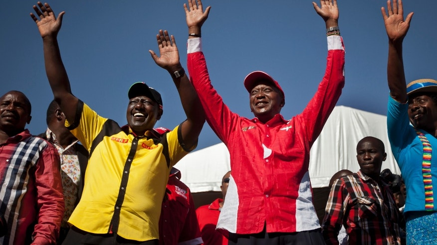 FILE - In this Saturday, March 2, 2013 file photo, then Kenyan Presidential candidate Uhuru Kenyatta, center right, and his running mate William Ruto, center left, greet the crowd as they arrive at the final election rally of Kenyatta's The National Alliance party at Uhuru Park in Nairobi, Kenya. Kenya's foreign minister Amina Mohamed said at a news conference Wednesday, Oct. 9, 2013 that no sitting president in the world has had to appear before a court, a statement that comes as Kenya appears to be laying the groundwork to avoid having President Uhuru Kenyatta appear at the International Criminal Court next month. (AP Photo/Ben Curtis, File)