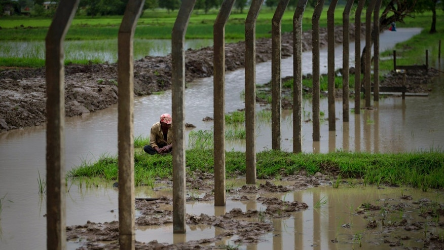 In this July 10, 2013 photo, a worker takes a break from fencing a paddy confiscated by Myanmar security forces in Dala, southeast of Yangon Myanmar. Despite sweeping reforms since a quasi-civilian government was installed two years ago, authorities not only have broad powers to seize land in the name of national interest, but to arrest, try and imprison small-scale farmers and political activists who stand up in protest. (AP Photo/Gemunu Amarasinghe)