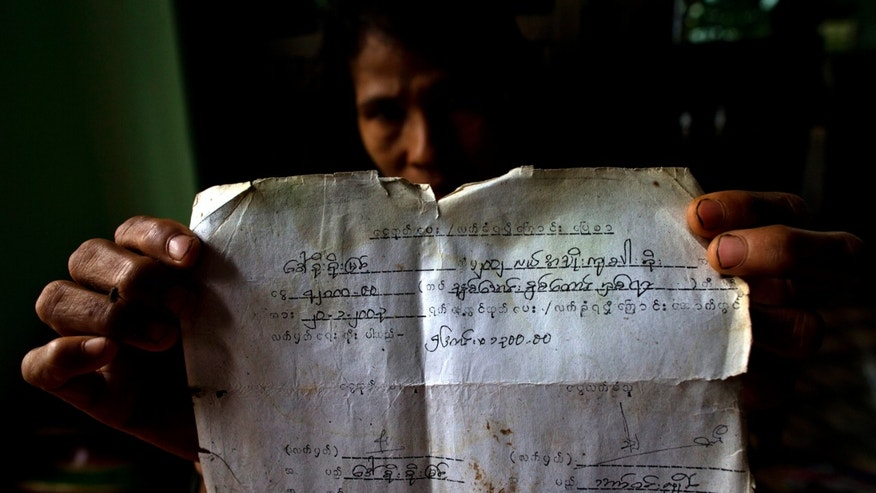 In this June 5, 2013 photo, a farmer displays a document proving her family's use of a paddy and payments made to the navy related to the land which was confiscated in 1992 by Myanmar security forces in Dala, Myanmar. Despite sweeping reforms since a quasi-civilian government was installed two years ago, authorities not only have broad powers to seize land in the name of national interest, but to arrest, try and imprison small-scale farmers and political activists who stand up in protest. (AP Photo/Gemunu Amarasinghe)