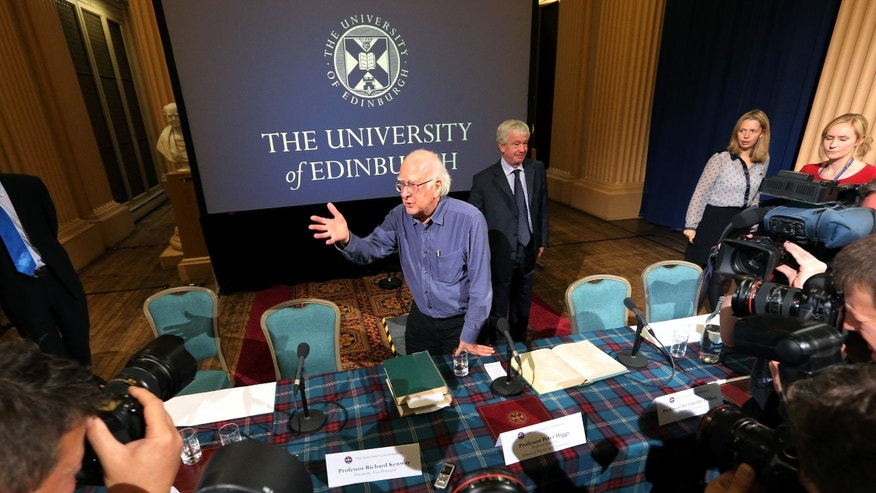Britain's Professor Peter Higgs, centre,  poses for the media, after a press conference,  in Edinburgh, Scotland Friday, Oct. 11, 2013. Nearly 50 years after they came up with the theory, but little more than a year since the world's biggest atom smasher delivered the proof, Professor Higgs and Belgian colleague Francois Englert won the Nobel Prize in physics Tuesday for helping to explain how matter formed after the Big Bang.  (AP Photo/Scott Heppell)