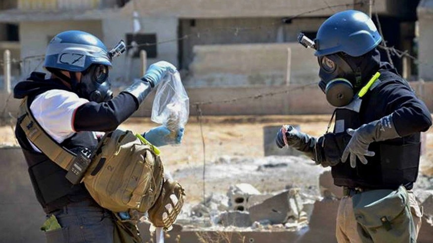 FILE - In this Wednesday, Aug. 28, 2013 citizen journalism file image provided by the United Media office of Arbeen, which has been authenticated based on its contents and other AP reporting, members of a chemical weapons investigation team take samples from sand near a part of a missile that is likely to be one of the chemical rockets, according to activists, in the Damascus countryside of Ain Terma, Syria. The Organization for the Prohibition of Chemical Weapons won the Nobel Peace Prize on Friday, Oct. 11, 2013, for working to eliminate the scourge that has haunted generations from World War I to the battlefields of Syria. (AP Photo/United Media office of Arbeen, File)