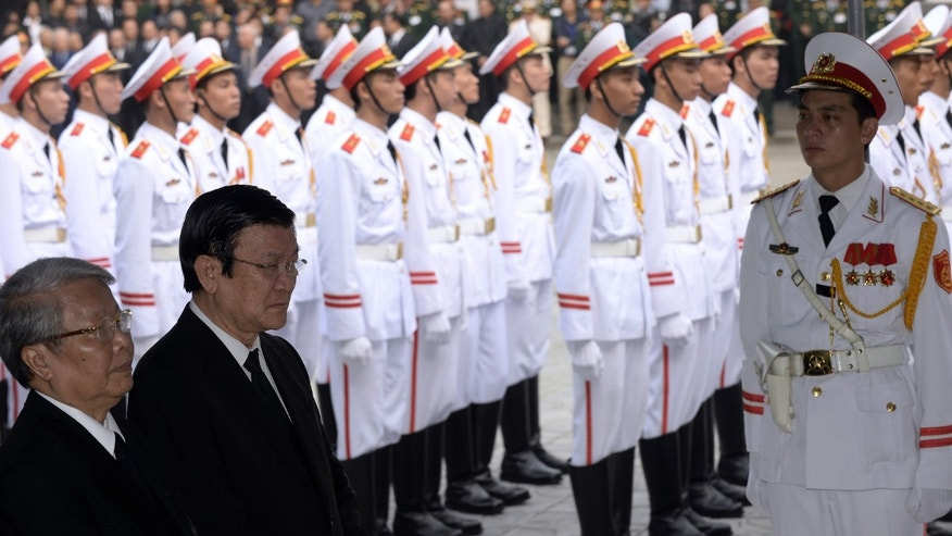 Vietnamese President Truong Tan Sang, second left, and former President Tran Duc Luong, left, pay respects to  late Gen. Vo Nguyen Giap at the National Funeral House in Hanoi, Vietnam Saturday, Oct. 12, 2013. Vietnam's top leaders gathered to pay their last respects to the military mastermind who drove the French and the Americans out of Vietnam, who died last week at 102. (AP Photo/Hoang Dinh Nam, Pool)