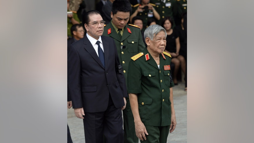 Former Communist Party General Secretaries Le Kha Phieu, right, and Nong Duc Manh arrive to pay respects to late Gen. Vo Nguyen Giap at the National Funeral House in Hanoi, Vietnam Saturday, Oct. 12, 2013. Vietnam's top leaders gathered to pay their last respects to the military mastermind who drove the French and the Americans out of Vietnam, who died last week at 102. (AP Photo/Hoang Dinh Nam, Pool)