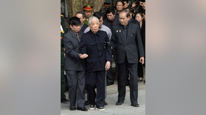 Former Communist Party Secretary General Do Muoi, front center, is helped to walk to pay respects to late Gen. Vo Nguyen Giap at the National Funeral House in Hanoi, Vietnam Saturday, Oct. 12, 2013. Vietnam's top leaders gathered to pay their last respects to the military mastermind who drove the French and the Americans out of Vietnam, who died last week at 102. (AP Photo/Hoang Dinh Nam, Pool)