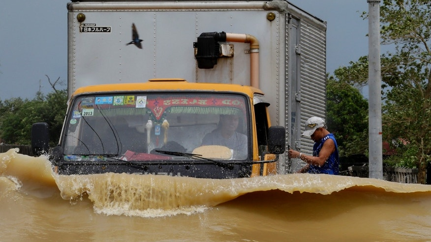 "A truck driver braves the raging floodwaters brought about by Typhoon ""Nari"" along a highway at  San Ildefonso township, Bulacan province, north of Manila, Philippines Saturday Oct. 12, 2013. At least eight people have been killed after Typhoon ""Nari"" battered across the northern Philippines Saturday, flooding villages and farms in the country's major rice-growing region, officials said. The typhoonwith 150 kilometers (94 miles) per hour winds and gusts of up to 185 kph (116 mph) forced U.S. Secretary of State John Kerry to call off his trip to the Philippines on Friday.(AP Photo/Bullit Marquez)"
