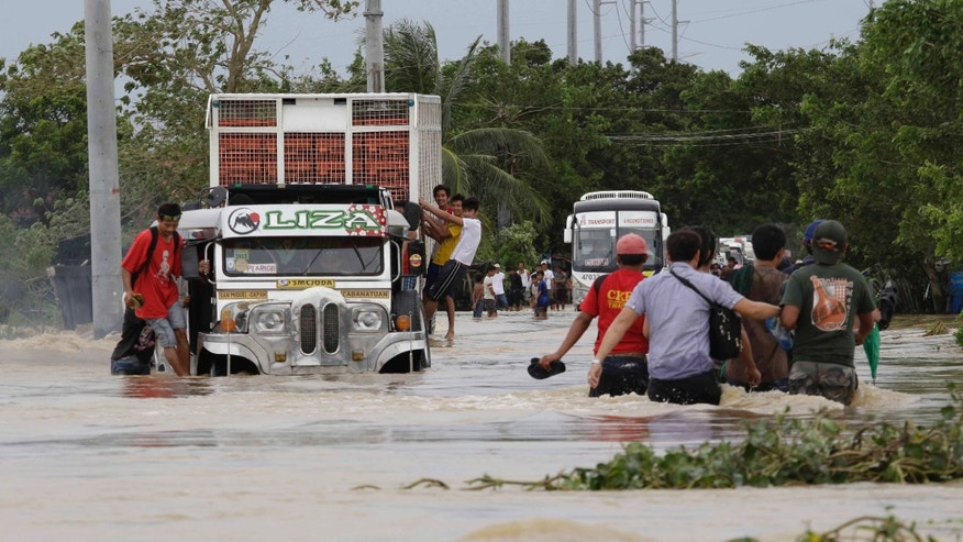 "Residents brave the raging floodwaters brought about by Typhoon ""Nari"" to get across a highway at  San Ildefonso township, Bulacan province, north of Manila, Philippines Saturday Oct. 12, 2013. At least eight people have been killed after Typhoon ""Nari"" battered across the northern Philippines Saturday, flooding villages and farms in the country's major rice-growing region, officials said. Typhoon Nari made a landfall into Aurora province northeast of Manila late Friday with 150 kilometers (94 miles) per hour winds and gusts of up to 185 kph (116 mph) with U.S. Secretary of State John Kerry calling off his trip to the Philippines on Friday due to the weather. (AP Photo/Bullit Marquez)"