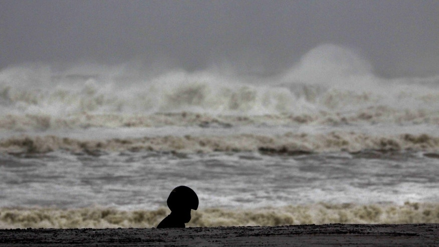 A man in a helmet walks past high waves of  the Bay of Bengal at Gopalpur beach in Ganjam district, about 200 kilometers  (125 miles) from the eastern Indian city Bhubaneswar, India, Saturday, Oct. 12, 2013. Strong winds and heavy rains pounded India's eastern coastline Saturday, as hundreds of thousands of people took shelter from a massive, powerful Cyclone Phailin expected to reach land in a few hours. (AP Photo/Biswaranjan Rout)