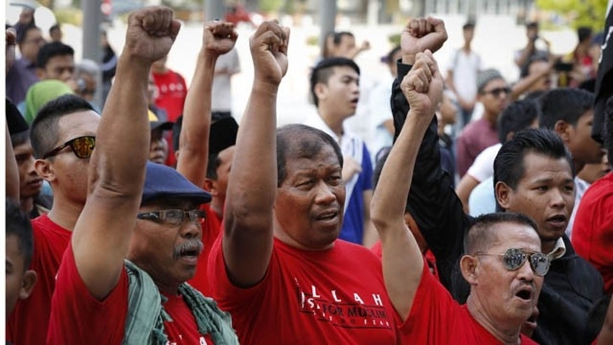 October 14, 2013: Muslim demonstrators chant slogans outside the Court of Appeal in Putrajaya, outside Kuala Lumpur, Malaysia, Monday. (AP Photo)
