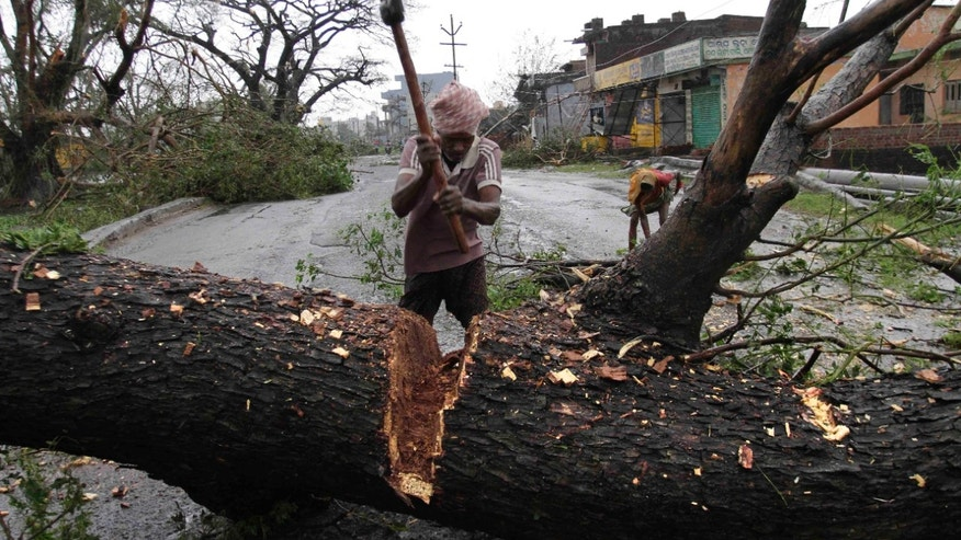 An Indian municipal workers cuts an uprooted tree from Cyclone Phailin to clear a main highway in Berhampur, India, Sunday, Oct. 13, 2013. An immense, powerful cyclone that lashed the Indian coast, forcing 500,000 people to evacuate and causing widespread damage, weakened Sunday after making landfall. Several people died in the rains that fell ahead of the storm, most killed by falling branches, Indian media reported, but the situation on the ground in many areas was still unclear after Cyclone Phailin slammed into the coast Saturday evening in Orissa state, where power and communications lines were down along much of the coastline. (AP Photo/Bikas Das)