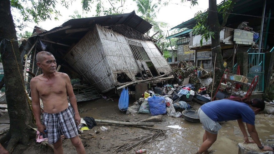 Residents stand outside their damaged house after typhoon Nari hit San Miguel town, Bulacan province, northern Philippines on Sunday, Oct. 13, 2013. The typhoon flooded villages and farms in the Philippines' major rice-growing region and has killed at least 13 people, officials said.  (AP Photo/Aaron Favila)