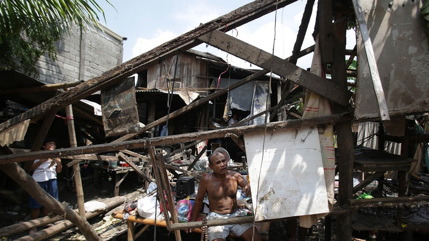 A Filipino resident sits inside his damaged house after typhoon Nari hit San Miguel town, Bulacan province, northern Philippines on Sunday, Oct. 13, 2013. The typhoon flooded villages and farms in the Philippines' major rice-growing region and has killed at least 13 people, officials said.  (AP Photo/Aaron Favila)