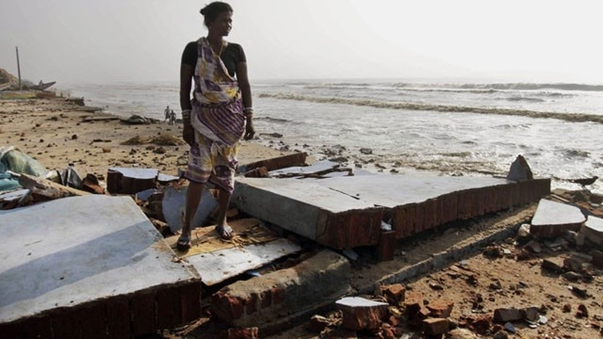 October 14, 2013: An Indian woman stands amidst debris of damaged houses in a cyclone affected village at a beach in Pudumpeta, Ganjam district, Orissa state, India Monday (AP Photo)