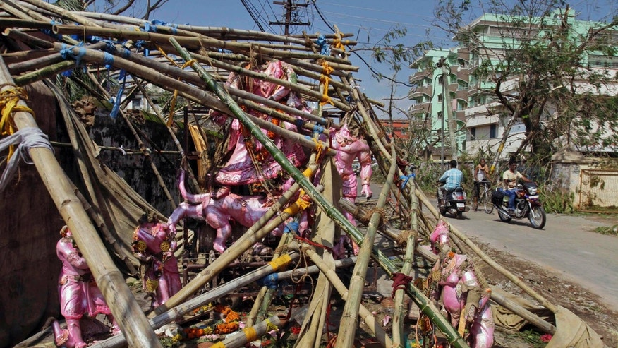 Indian people ride past idols of Hindu gods and goddesses damaged during the Cyclone Phailin at a temporary worship venue in Berhampur in Ganjam district, Orissa state, India, Monday, Oct. 14, 2013. A mass government evacuation of nearly 1 million people spared India the widespread deaths many had feared from the powerful weekend cyclone, which destroyed hundreds of millions of dollars' worth of crops and tens of thousands of homes. (AP Photo/Bikas Das)