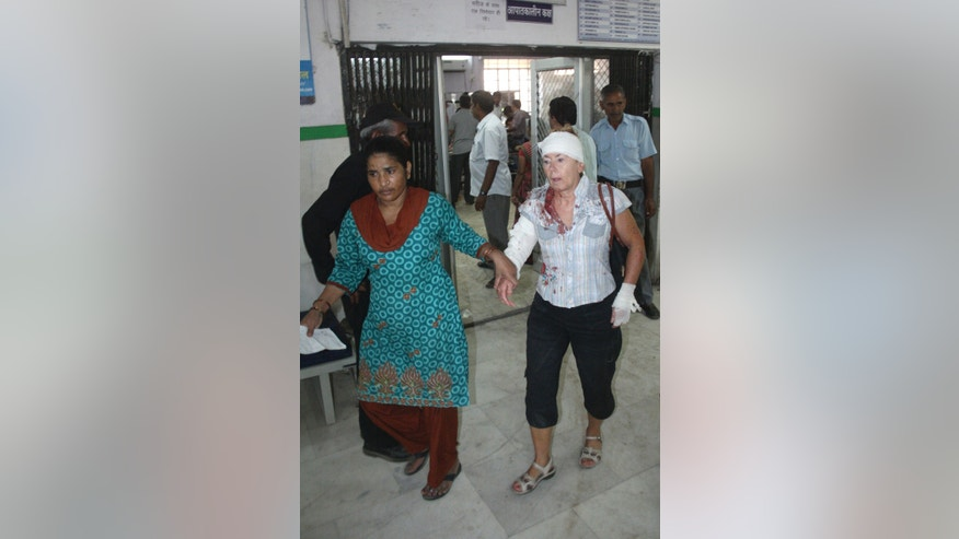 A French tourist, right, injured after a tour bus she was on was hit by a truck and overturned, is helped as she receives treatment at the Mathura Das Mathur (MDM) hospital in Jodhpur, Rajasthan state, India, Monday, Oct. 14, 2013. Police said four French tourists are in critical condition and about 30 other French tourists were injured in the accident. (AP Photo/ Mohammed Sharif)