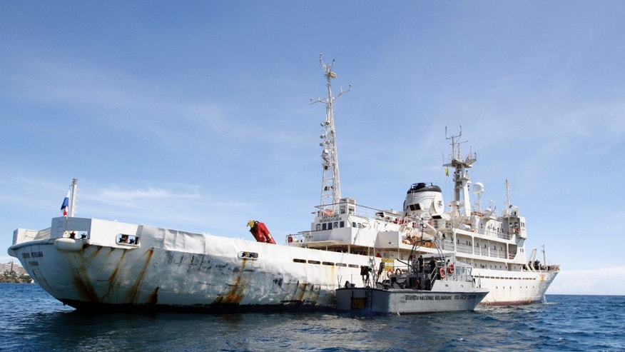A Venezuelan Coast Guard boat sits next to  the 285-foot survey ship Teknik Perdana docked near the shore in Margarita Island, Venezuela, Sunday Oct. 13, 2013. The  U.S.-chartered oil exploration ship seized by the Venezuelan navy in Caribbean waters disputed with neighboring Guyana arrived at Venezuela's Margarita Island on Sunday. Venezuelan authorities said the ship's 36 crew members, including five U.S. citizens and two Brazilians, would be held on board while an investigation continued. (AP Photo/Gustavo Granado)