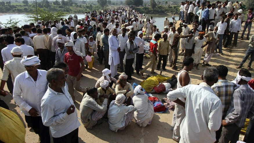 Indian villagers gather after a deadly stampede on a bridge across the Sindh River in Datia district in Madhya Pradesh state, India, Sunday, Oct. 13, 2013. A stampede by masses of Hindu worshippers left scores of people dead on a bridge they had been crossing to reach a temple in central India, police said. (AP Photo)