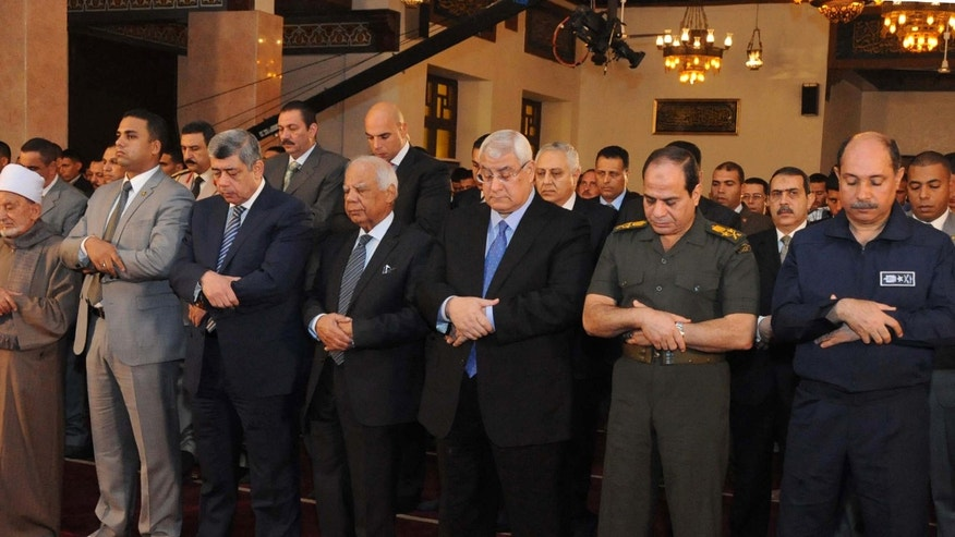 This image released by the Egyptian Presidency shows interim President Adly Mansour, center, interim Prime Minister Hazem el-Beblawi, fourth from left, and Defense Minister Gen. Abdel-Fattah el-Sissi, second from right, pray on the first day of Eid al-Aha, or Feast of Sacrifice, in Cairo, Egypt, Tuesday, Oct. 15, 2013.