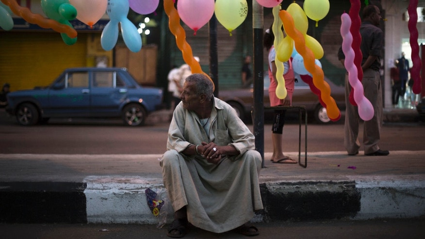 An Egyptian man waits for the morning prayer on a street decorated with balloons near the Sayyida Zeinab mosque on the first day of Eid al-Ahda in Cairo, Egypt, Tuesday, Oct. 15, 2013. Muslims worldwide are celebrating Eid al-Adha, or the Feast of the Sacrifice, by sacrificial killing of sheep, goats, cows or camels. The slaughter commemorates the biblical story of Abraham, who was on the verge of sacrificing his son to obey God's command, when God interceded by substituting a ram in the child's place. (AP Photo/Manu Brabo)