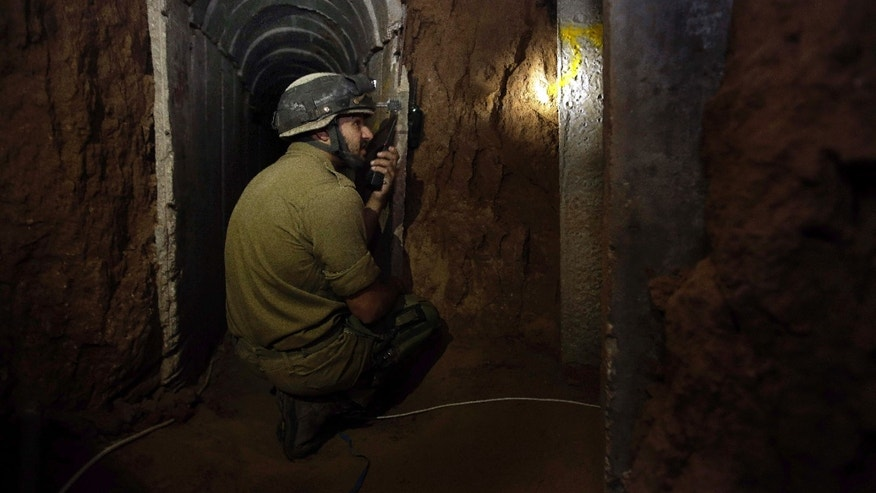 Israeli soldier kneels in a tunnel discovered near the Israel Gaza border, Sunday, Oct. 13, 2013. The Israeli military said Sunday it discovered a concrete-lined tunnel dug from the Hamas-controlled Gaza Strip into Israel, alleging militants planned to use it to attack or kidnap Israelis. In response, the military froze the transfer of all construction materials to the Palestinian territory, the army said. (AP Photo/Tsafrir Abayov)