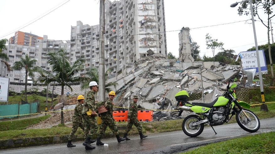 Soldiers walk past the remains of a 22-story building that imploded, in Medellin, Colombia, Monday, Oct. 14, 2013. Heavy rains and fears an adjacent building could fall have forced a halt in the search for 11 people trapped in the ruins of a collapsed Colombian apartment tower. The city's emergency management director says he hasn't lost hope that someone has survived in the 22-story building that imploded on Saturday night, but that the odds are against it, given the weight of the rubble. (AP Photo /Luis Benavides)