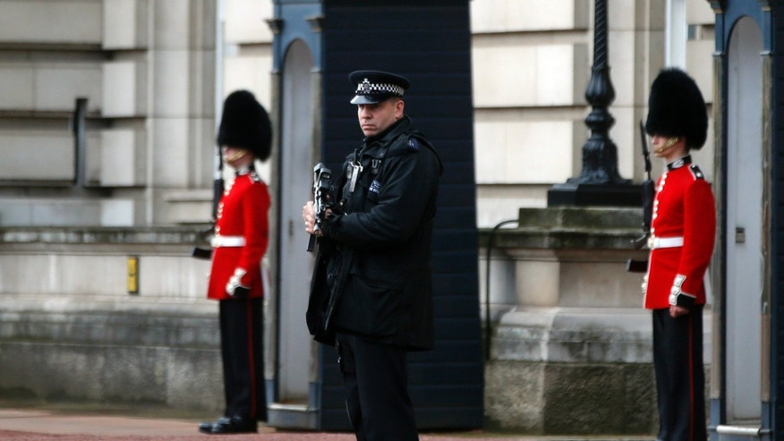 A British police officer guards the grounds of Buckingham Palace in central London, Monday, Oct. 14, 2013. British police arrested a man with a knife after he tried to dart through a gate at Buckingham Palace in London on Monday. The palace said Queen Elizabeth II was not in residence. Breaches of royal security are rare, but just a month ago police arrested two men over a suspected break-in at the palace. (AP Photo/Lefteris Pitarakis)