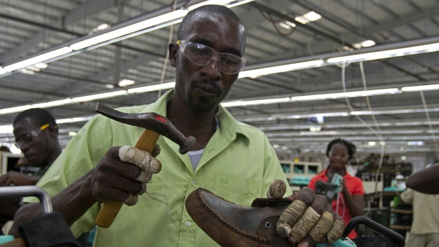 FILE - In this Jan. 11, 2012 file photo, Renel Prophete, 33, works on a pair of boat shoes at a local clothing and shoe factory, Caracol Industrial Park, during a visit by former U.S. President Bill Clinton in Ouanaminthe, on the outskirts of Cap Haitien, Haiti. A labor rights group is accusing clothing manufacturers in Haiti of frequently cheating workers out of their meager wages. The U.S.-based Worker Rights Consortium says in a report that workers receive an average of 32 percent less than what they should. (AP Photo/Dieu Nalio Chery, File)