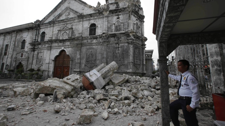 A private guard stands near the damaged Basilica of the Holy Child following a 7.2-magnitude earthquake that hit Cebu city in central Philippines and toppled the bell tower of the Philippines' oldest church Tuesday, Oct. 15, 2013. The tremor collapsed buildings, cracked roads and toppled the bell tower of the church Tuesday morning, causing multiple deaths across the central region and sending terrified residents into deadly stampedes. (AP Photo/Bullit Marquez)