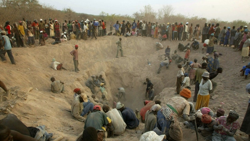 File - in this file photo taken Wednesday, Nov. 1, 2006, gangs of illegal miners dig for diamonds in Marange, eastern Zimbabwe. The wealth enjoyed by just a few comes, at least in part, from the vast Marange diamond field that was exposed by an earth tremor in 2006.  The Marange deposit is the biggest diamond field found in Africa for a century, estimated to be worth some billions of dollars, but as most Zimbabweans remain mired in poverty, questions are being asked about where all the money went and who benefited. (AP Photo/Tsvangirayi Mukwazhi,  FILE)