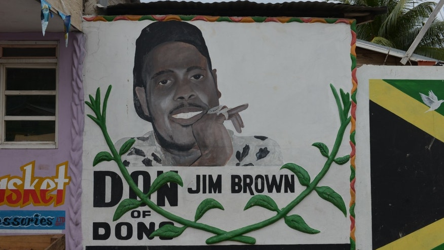 In this Oct. 12, 2013 photo, a painted mural depicting famed Jamaican gang leader Lester Lloyd Coke, better known as Jim Brown, takes up a stretch of wall next to a casket supplier in the Denham Town slum, in Kingston, Jamaica. Police are erasing street-side images of leaders of Jamaica's violent underworld in hopes of changing the culture of gang-steeped West Kingston as they make progress in reducing some of the lawlessness that has defined the area for decades. (AP Photo/David McFadden)