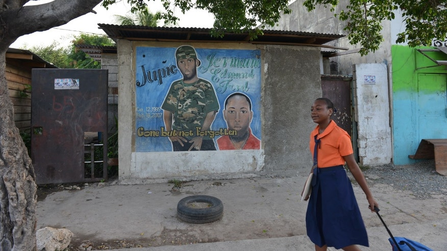 In this Oct. 9, 2013 photo, a schoolgirl walks past a mural memorializing a young man cut down by bullets in West Kingston, Jamaica. Police are hoping to beat back the lawless culture that has defined the gang-steeped area for decades, erasing images of famed leaders of Jamaica's violent underworld. Also slated for removal are murals of lesser-known gunmen memorialized where their bodies fell. (AP Photo/David McFadden)