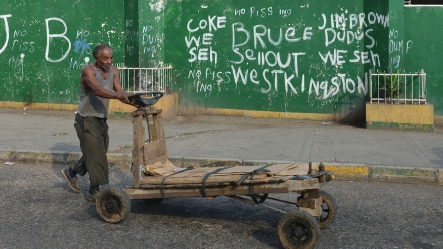 In this Oct. 12, 2013 photo, a market vendor wheels a handcart down a prominent corner in West Kingston, Jamaica, where graffiti scrawls vow allegiance to former Shower Posse gang leaders Christopher 'Dudus' Coke and his father, Lester Lloyd Coke, better known as Jim Brown. The crime boss most often glorified on the streets is Jim Brown, whose ruthless syndicate was responsible for 1,400 murders on the U.S. East Coast, according to the FBI. (AP Photo/David McFadden)