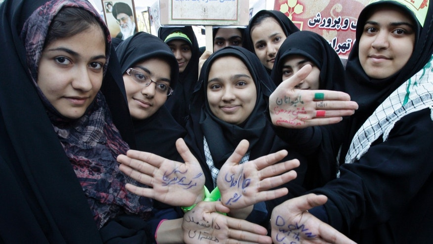 "In this picture taken on Friday, Nov. 2, 2012, Iranian school girls show their hands with writing in Persian in support supreme leader Ayatollah Ali Khamenei, denouncing the U.S. and one of them with word ""Nuclear Scientist"" in an annual state-backed rally in front of the former U.S. Embassy in Tehran, Iran, commemorating 33rd anniversary of the embassy takeover by militant students. On Nov. 4, 1979, students who believed the embassy was a center of plots against Iran held 52 Americans hostages for 444 days, and the US severed formal diplomatic ties in response. In a sharp counterpoint to the Western outreach by President Hassan Rouhani's government, hard-line factions in Iran have amplified their bluster and backlash in messages that they cannot be ignored in any diplomatic moves with Washington either in the nuclear talks or beyond. (AP Photo/Vahid Salemi)"