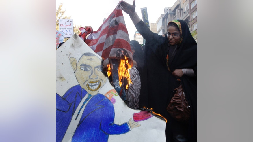 In this picture taken on Friday, Nov. 2, 2012, a female Iranian demonstrator holds up a burning representation of the U.S. flag while a caricature of President Barack Obama is set on fire, in an annual state-backed rally in front of the former U.S. Embassy in Tehran, Iran, commemorating 33rd anniversary of the embassy takeover by militant students. On Nov. 4, 1979, students who believed the embassy was a center of plots against Iran held 52 Americans hostages for 444 days, and the US severed formal diplomatic ties in response. In a sharp counterpoint to the Western outreach by President Hassan Rouhani's government, hard-line factions in Iran have amplified their bluster and backlash in messages that they cannot be ignored in any diplomatic moves with Washington either in the nuclear talks or beyond.(AP Photo/Vahid Salemi)