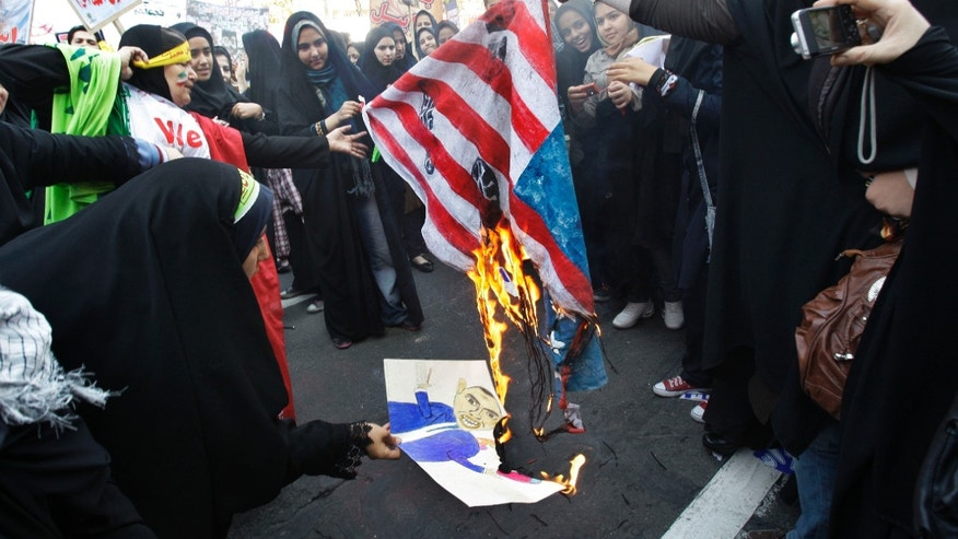 FILE-- In this Friday, Nov. 2, 2012, file photo, Iranian female demonstrators burn a representation of U.S. flag, and a caricature of President Barack Obama, in an annual state-backed rally in front of the former U.S. Embassy in Tehran, Iran, commemorating 33rd anniversary of the embassy takeover by militant students. On Nov. 4, 1979, students who believed the embassy was a center of plots against Iran held 52 Americans hostages for 444 days, and the US severed formal diplomatic ties in response. In a sharp counterpoint to the Western outreach by President Hassan Rouhani's government, hard-line factions in Iran have amplified their bluster and backlash in messages that they cannot be ignored in any diplomatic moves with Washington either in the nuclear talks or beyond. (AP Photo/Vahid Salemi, File)